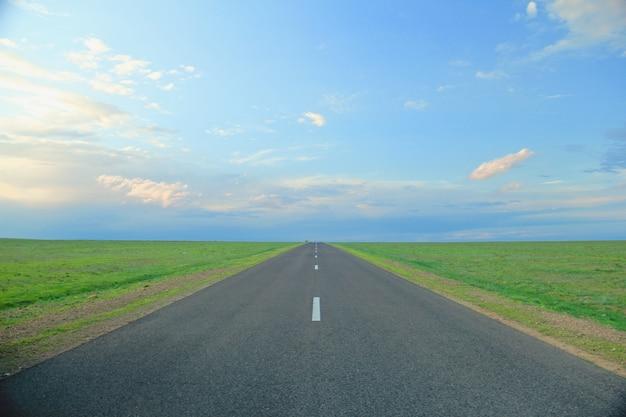 Straße umgeben von grasfeldern unter einem blauen himmel Kostenlose Fotos