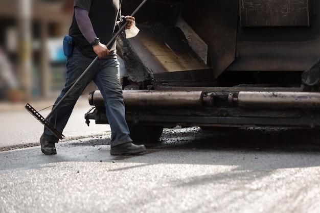 Straßenbauarbeiter, die asphaltstraße reparieren. Premium Fotos
