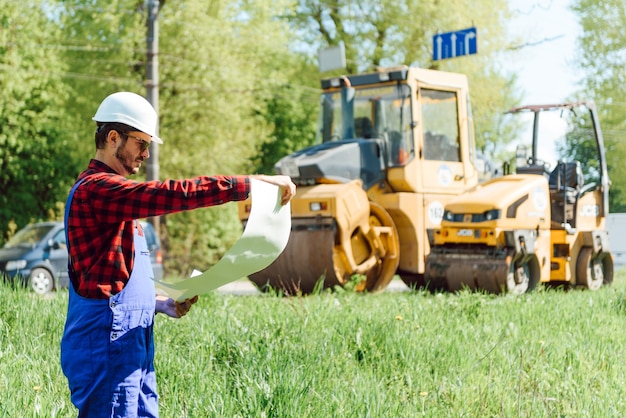 Straßenbauarbeiter in der nähe von asphaltfertiger. straßenreparatur. straßenarbeiter in der nähe der eisbahn. Premium Fotos