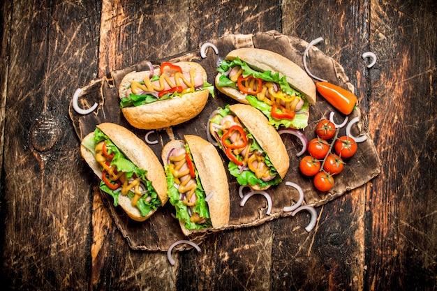 Straßenessen. hot dogs mit kräutern, gemüse und heißem senf auf holztisch. Premium Fotos