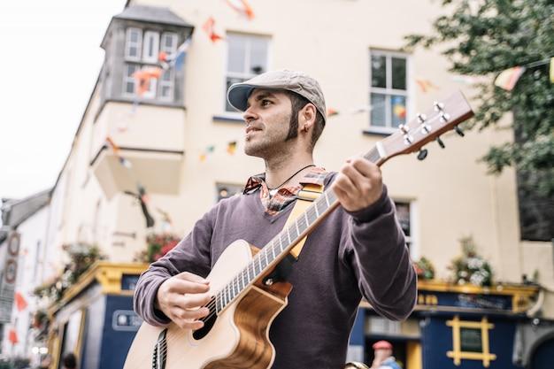Straßenkünstlermann, der die gitarre spielt Premium Fotos