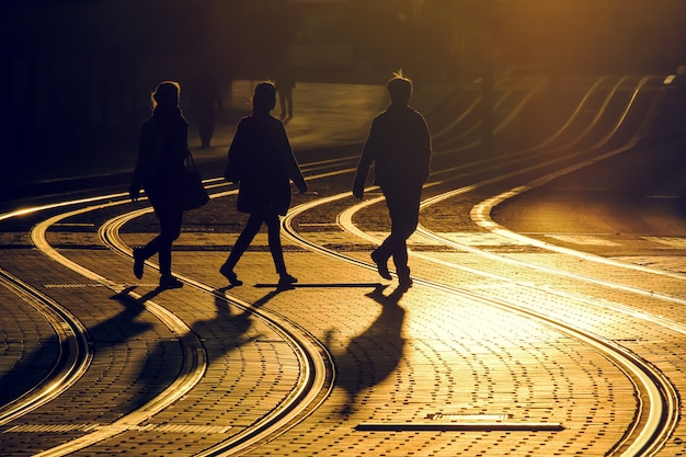 Straßenphotographie von freunden machen einen spaziergang auf trameisenbahn während des sonnenuntergangs in der bordeauxstadt, frankreich. Premium Fotos