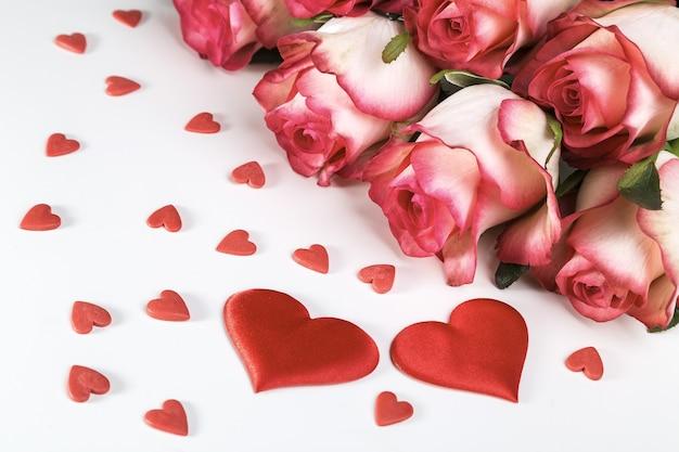Strauß der hellen rosen und der roten herzen auf einem weißen hintergrund. valentinstag grußkarte. Premium Fotos