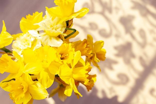 Strauß narzissen. schöner durchbrochener schatten auf dem tisch. erste frühlingsblumen. Premium Fotos