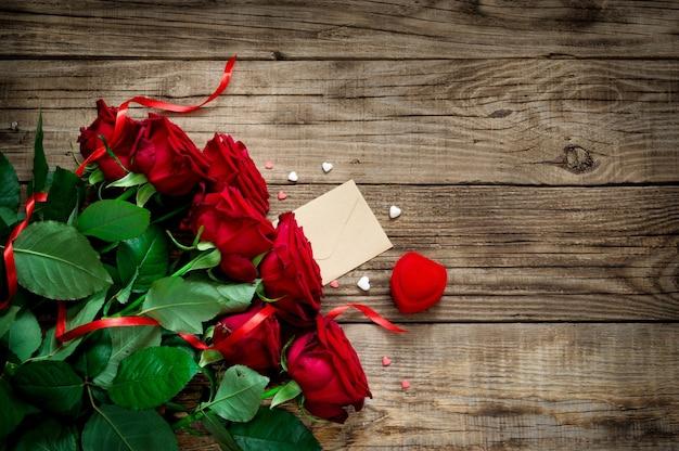 Strauß rote frische rosen auf einem schönen hölzernen hintergrund mit rotem band, geschenk, herz. flache lage. kopierfläche. Premium Fotos