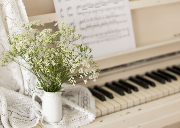 Strauß wildblumen auf weißem klavier mit noten. retro foto Premium Fotos