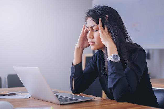 Stressige geschäftsfrau, die im büro müde und gelangweilt arbeitet. Premium Fotos
