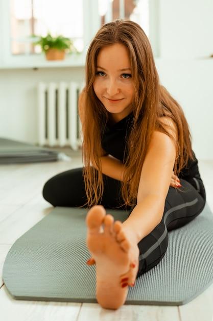 Stretching-training. gesunder lebensstil. junges schönes mädchen in der schwarzen uniform tut, übung ausdehnend. akroyoga, yoga, fitness, training, sport. Premium Fotos