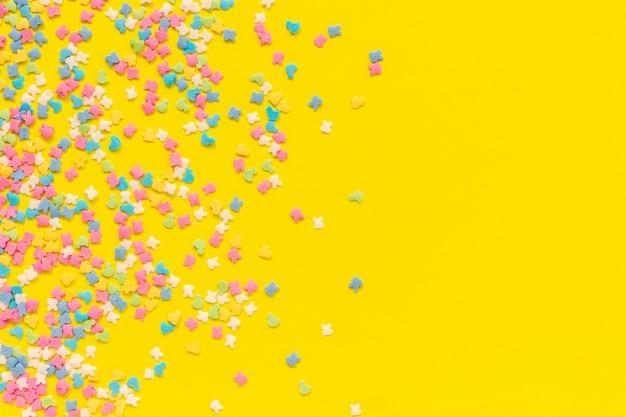 Streuen der mehrfarbigen süßigkeitenbelagbehandlung auf gelbem papier. festlicher hintergrund Premium Fotos