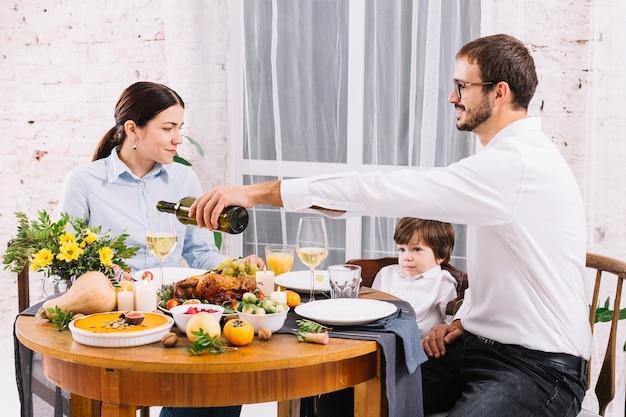 Strömender wein des mannes im glas beim speisen mit familie Kostenlose Fotos