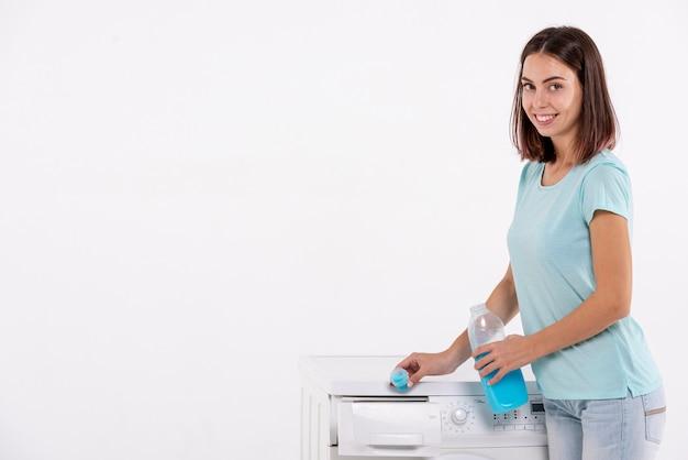 Strömendes reinigungsmittel der mittleren schussfrau in waschmaschine Kostenlose Fotos