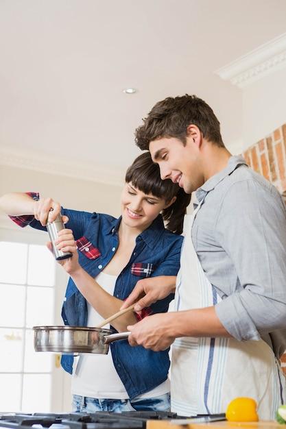 Strömendes salz der frau in gerät während mann, der eine mahlzeit in der küche zubereitet Premium Fotos