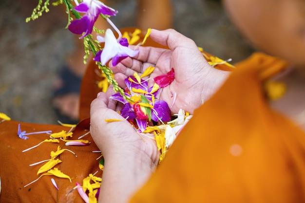 Strömendes wasser der leute zu den buddhistischen mönchen und gibt segen in jährlichem festival thailands songkran im buddhistischen tempel Premium Fotos