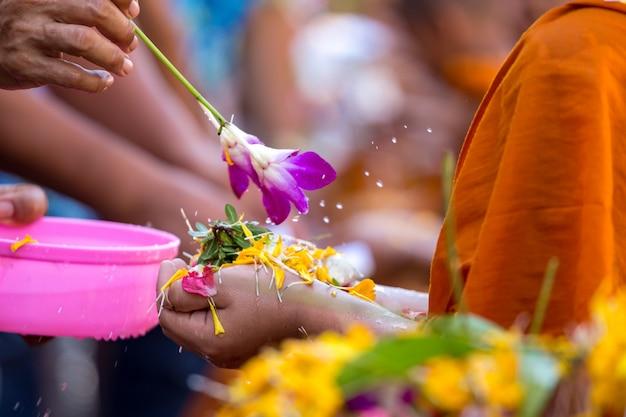 Strömendes wasser der leute zu den buddhistischen mönchen und gibt segen in thailand Premium Fotos