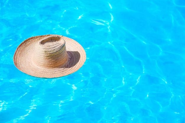 Strohhut auf der oberfläche des blauen klaren swimmingpools Premium Fotos