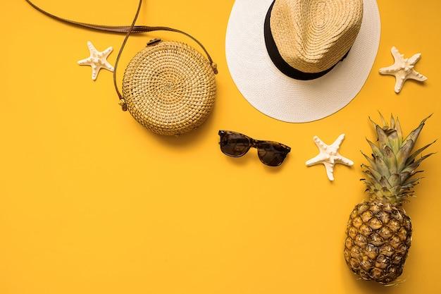 Strohhut, bambustasche, sonnenbrille, ananas und seestern über gelb Premium Fotos