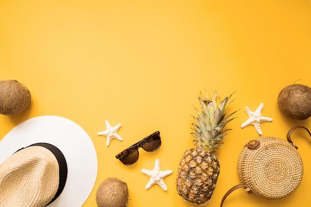 Strohhut, bambustasche, sonnenbrille, kokosnuss, ananas, muscheln und seestern über gelb Premium Fotos