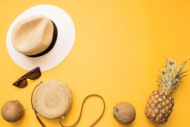 Strohhut, bambustasche, sonnenbrille, kokosnuss, ananas über gelb Premium Fotos