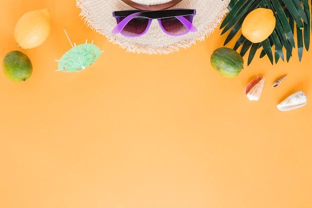Strohhut mit sonnenbrille, muscheln und früchten Kostenlose Fotos