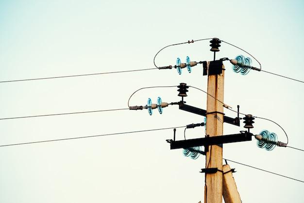Stromleitungen auf hintergrund der nahaufnahme des blauen himmels. elektrische nabe auf der stange. strom ausrüstung mit exemplar. drähte der hochspannung im himmel. elektrizitätswirtschaft. Premium Fotos