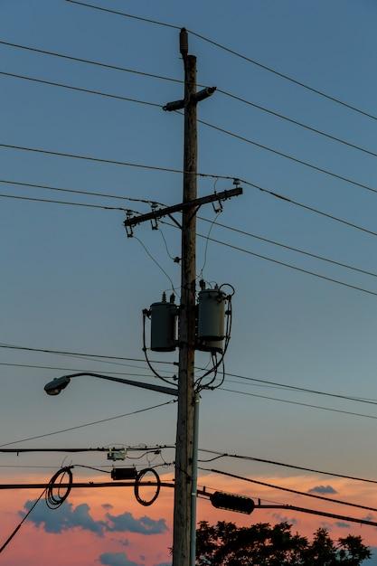 Strompfosten mit sonnenuntergang, schattenbild Premium Fotos