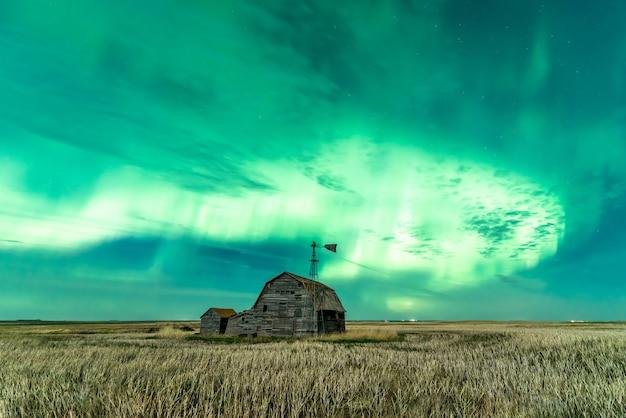 Strudel der hellen nordlichter über weinlesestallbehältern und -windmühle Premium Fotos