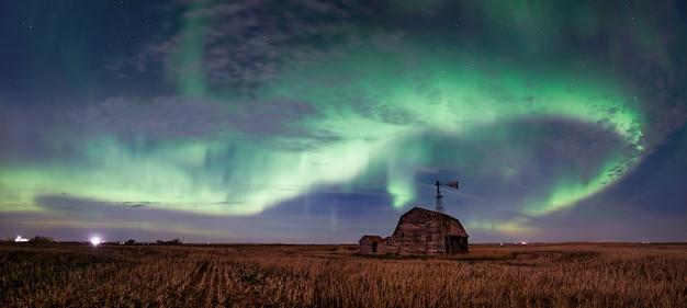 Strudel von hellen nordlichtern über weinlesescheune, behältern, windmühle und stoppeln in saskatchewan, kanada Premium Fotos