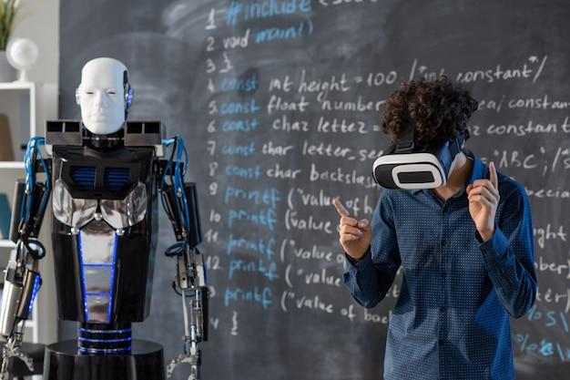 Student im vr-headset steht an der tafel mit der formel und bedient sich des automatisierungsroboters durch virtuelle steuerung Premium Fotos