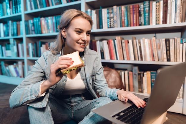 Student isst sandwich und benutzt laptop. Premium Fotos