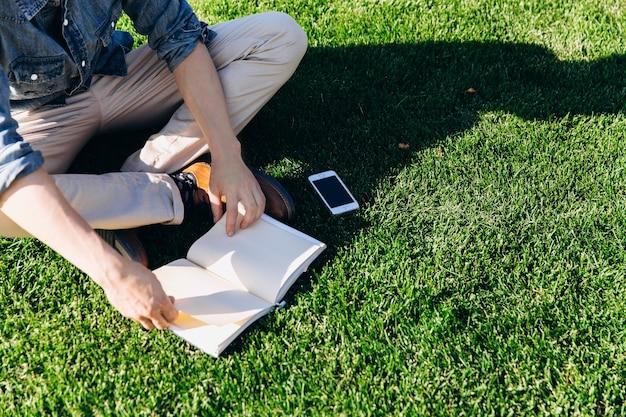 Student liest ein buch, das auf dem grünen rasen vor der modernen bibliothek sitzt Premium Fotos