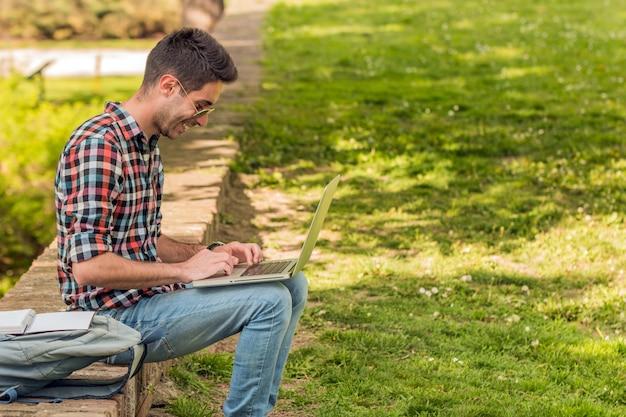 Student mit buch student, der hausarbeit im park tut. Premium Fotos