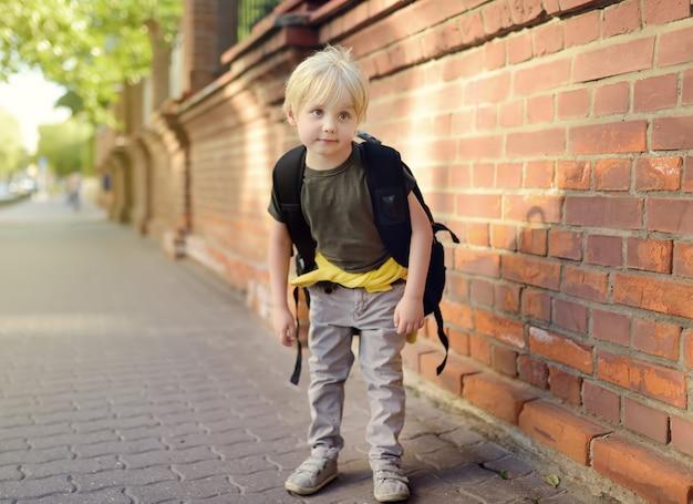 Student mit großem rucksack nahe dem schulgebäude. Premium Fotos