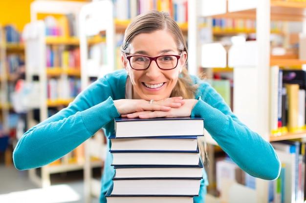 Student mit stapel von büchern lernend in der bibliothek Premium Fotos