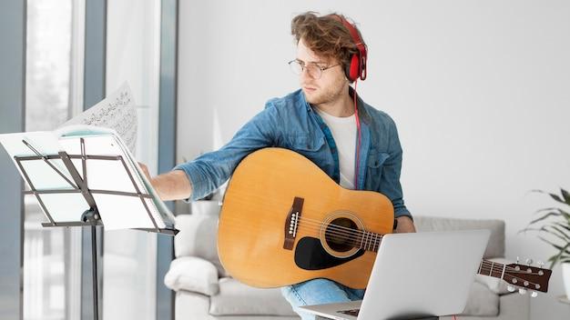 Student spielt gitarre und trägt kopfhörer Premium Fotos