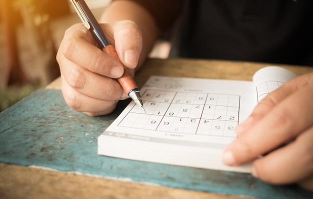 Student versucht sudoku mit farbbleistift als hobby bei im freien zu lösen Premium Fotos