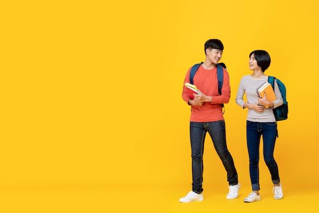 Studenten, die buch halten und beim gehen sprechen Premium Fotos
