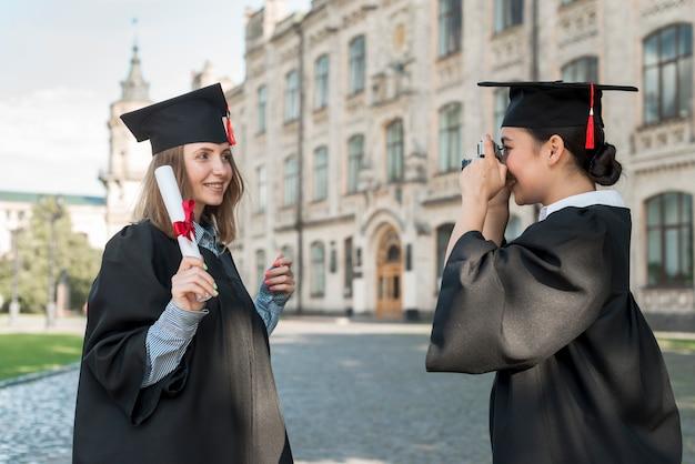 Studenten, die foto von einander an der staffelung machen Kostenlose Fotos