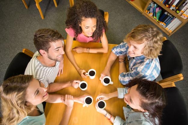 Studenten, die kaffeetassen auf tabelle halten Premium Fotos