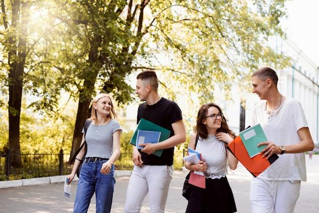 Studenten, die nach vorlesungen und seminaren zum studentenwohnheim gehen, ideen austauschen und sich über den unterricht unterhalten. studenten, die am abend in den park gehen Premium Fotos