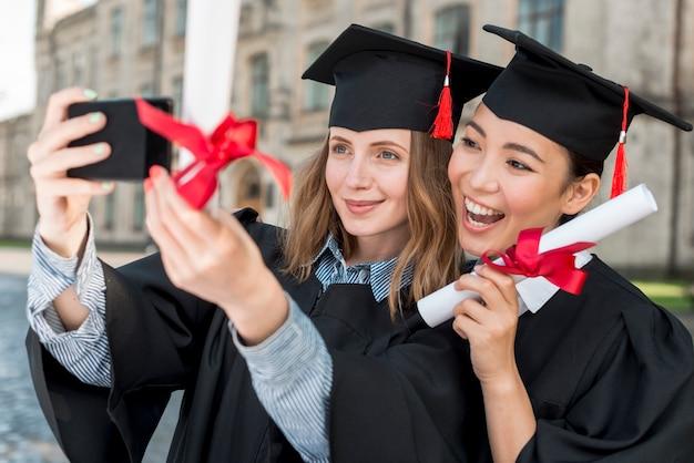Studenten, die selfie am abschluss nehmen Kostenlose Fotos