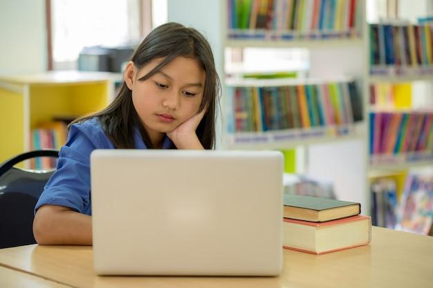Studenten, die sich auf bildung in der bibliothek konzentrieren Kostenlose Fotos