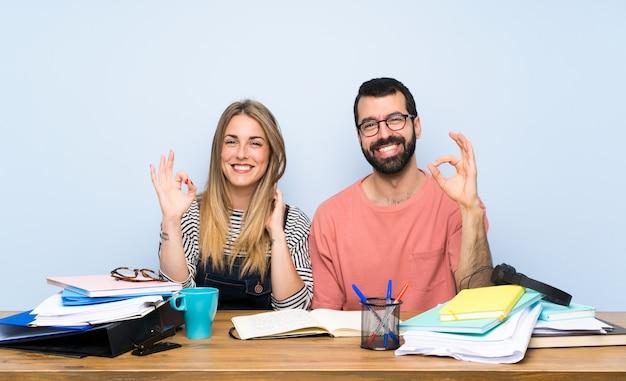 Studenten mit vielen büchern, die okayzeichen mit den fingern zeigen Premium Fotos