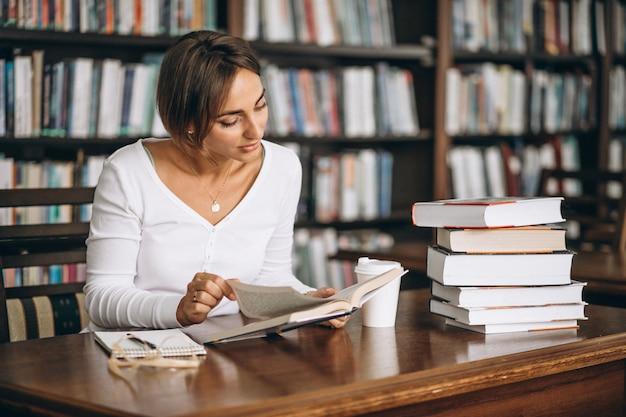 Studentenfrau, die an der bibliothek studiert und kaffee trinkt Kostenlose Fotos