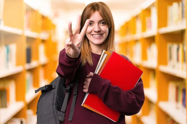 Studentenfrau, die drei auf unfocused hintergrund zählt. zurück zur schule Premium Fotos