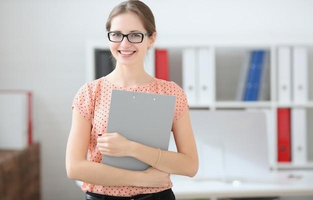 Studentenfrau, die eine tablette für anmerkungen in den händen im publikum hält Premium Fotos