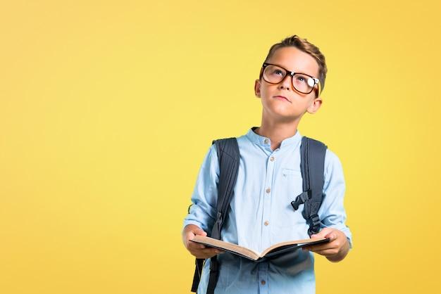 Studentenkind mit dem rucksack und gläsern, die ein buch auf gelbem hintergrund halten. zurück zur schule Premium Fotos
