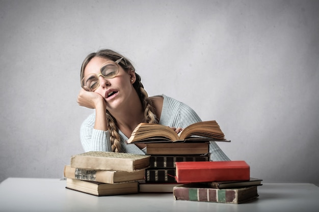 Studentenmädchen, das auf bücher einschläft Premium Fotos