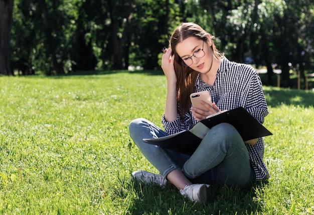 Studentenmädchen untersucht ihren smartphone mit einem ordner in ihren händen, die auf dem gras im park sitzen Premium Fotos