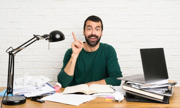 Studentenmann, der eine idee zeigt den finger oben denkt Premium Fotos
