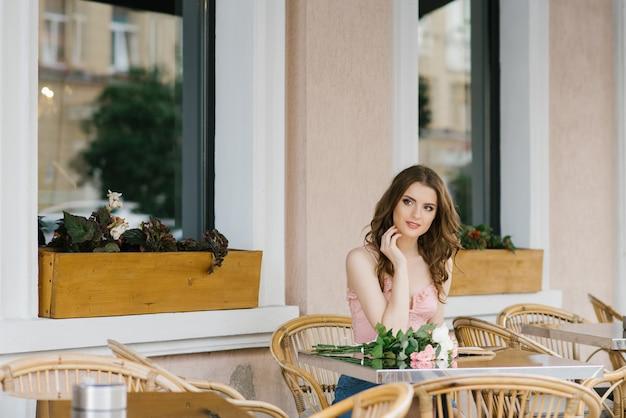 Studentin auf eine romantische art, die an einem tischstraßencafé sitzt Premium Fotos